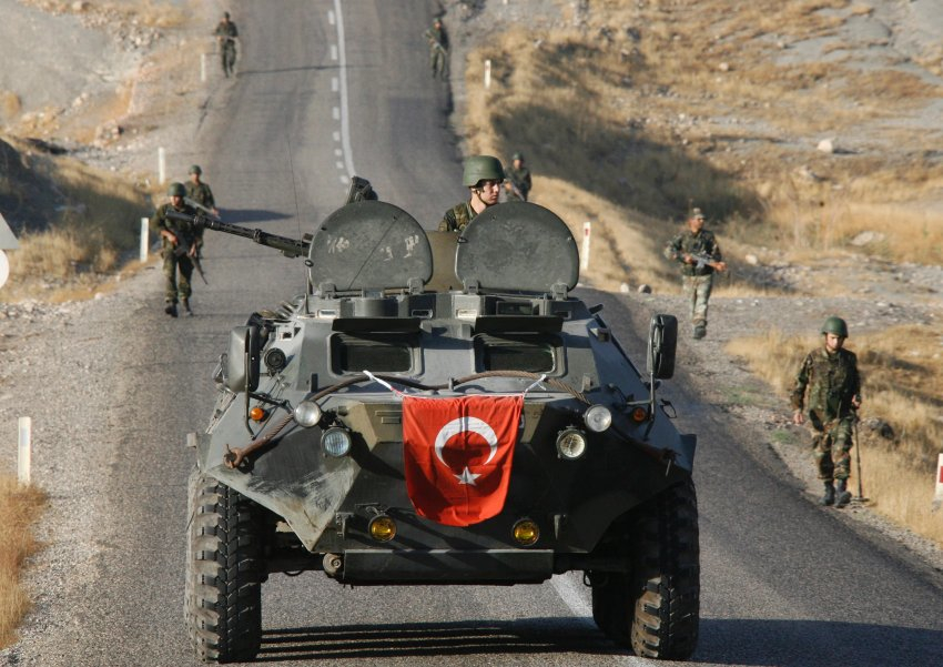 Turkish soldiers patrol and search for mines on a road surrounded by rugged mountains in south-eastern province of Sirnak