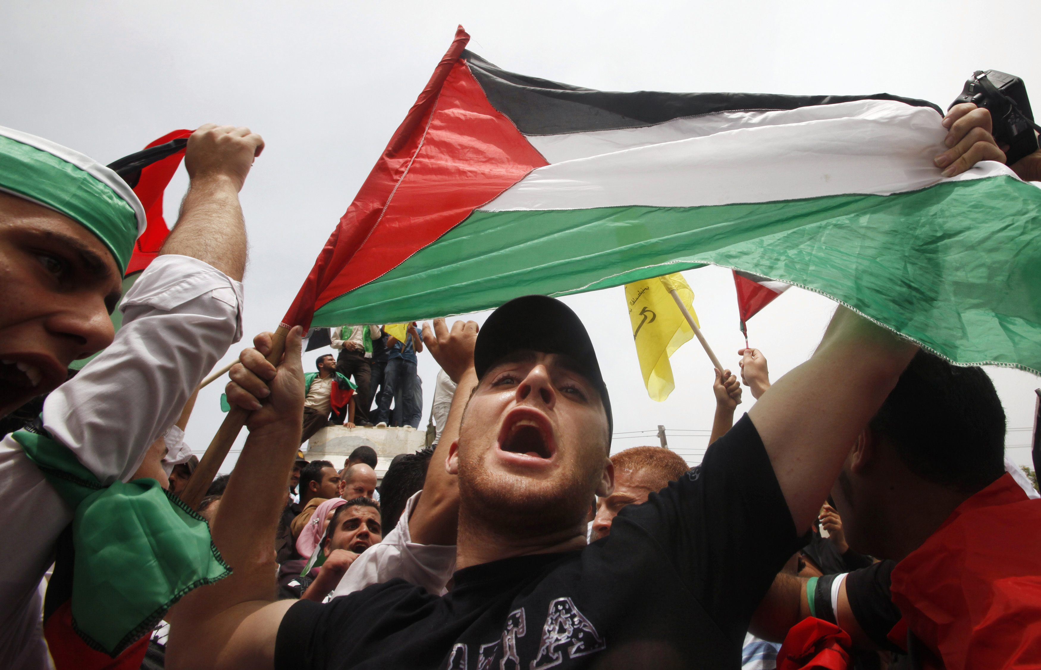 Palestinian holds up flag as he celebrates reconciliation agreement between rival Palestinian factions Fatah and Hamas during rally in Gaza City